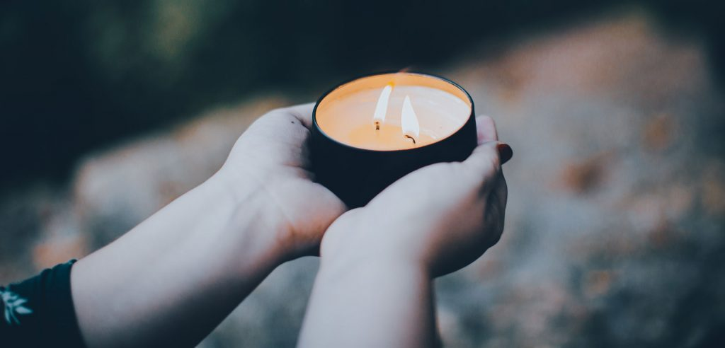 two hands holding a tea light candle
